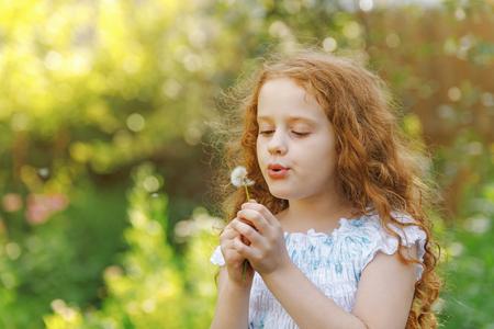 春の公園でタンポポを吹く小さなカーリーの女の子。