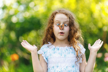 Surprised girl with a butterfly on her nose, focus on a girl face. Stock Photo