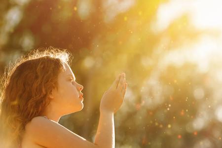 Mała dziewczynka z modlitwą. Pokój, nadzieja, koncepcja marzeń.