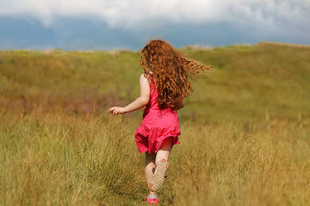 Curly hair girl run on the wheat field at sunset. Freedom, childhood, lifestyle concept.