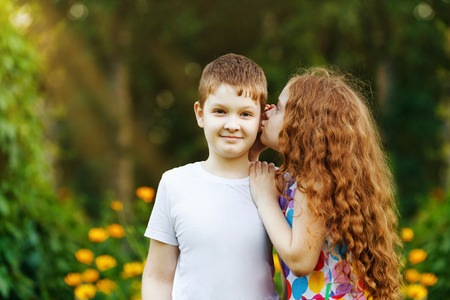 Cute friends embracing and whispers in spring park. Stock Photo