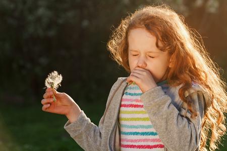 屋外の春の花のためにくしゃみとアレルギーを持つ小さな女の子。医療の概念。