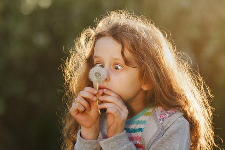 小さな女の子は春に公園でタンポポを見て刈りを信頼していません。 写真素材