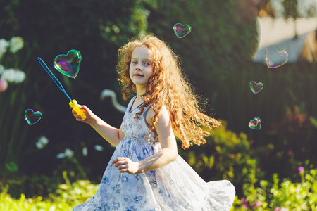 Curly girl playing with soap bubbles. Valentines day concept.