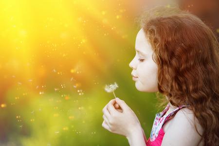 Dente-de-leão de sopro bonito da menina do cabelo encaracolado na luz do por do sol. Saúde, conceito de estilo de vida. Foto de archivo - 93610586