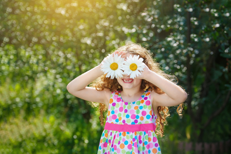 Happy toothless child with daisy eyes in a spring garden. Medical, healthy and lifestyle concept.