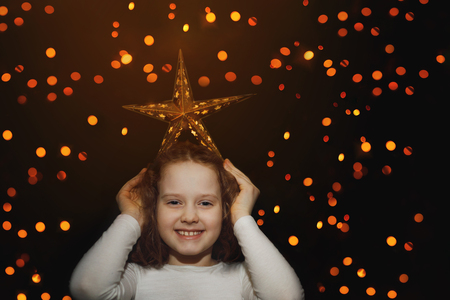 Cute girl hold star on her head and have fun. Dreaming, winner, chrisrmas, happy childhood concept.