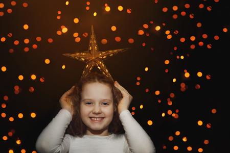 Netter Mädchengriffstern auf ihrem Kopf und haben Spaß. Träumen, Sieger, Weihnachten, glückliches Kindheitskonzept. Standard-Bild - 93928617