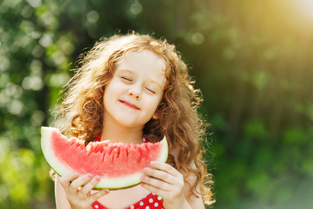 Girl eating watermelon enjoying closing her eyes. Diet, vitamins, healthy food concept.