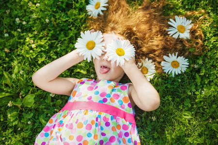 Child with daisy eyes with rainbow dress shows tongue and lying on green grass at green grass.