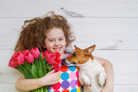 Laughing girl hugging a puppy and holding red tulips. Happy mothers, father or valentines days concept.