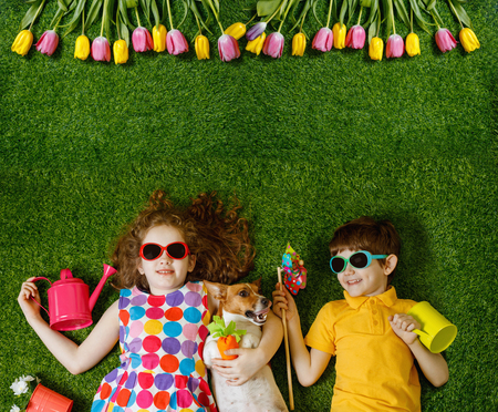 Little girl and boy, and his dog lying on green grass. Spring, Easter background. Top view portrait.