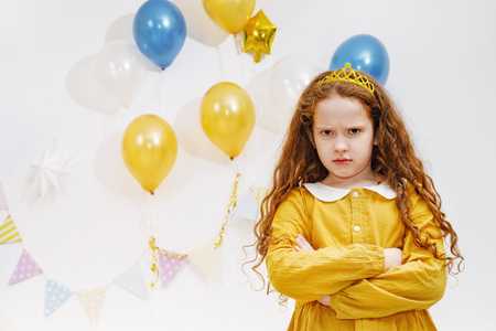 Emotional princess girl with angry expression on face in birthday party. Stock Photo