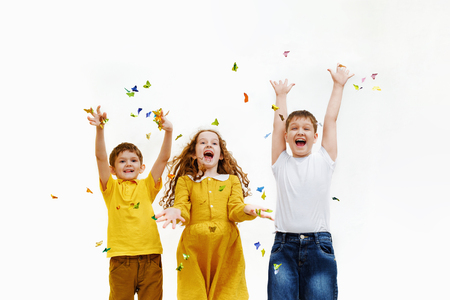 Happy friends on carnival party, catched confetti butterfly. Happy childhood, healthy, holiday concept.