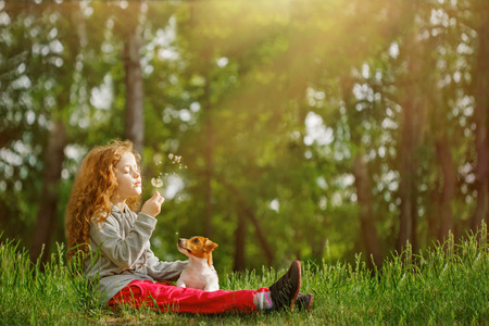 Little girl embracing his jack russell and blowing dandelion. Happy childhood concept. Stock Photo
