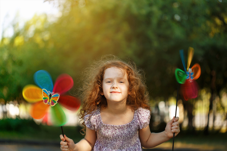 Laughing girl holding a rainbow pinwheel toys.