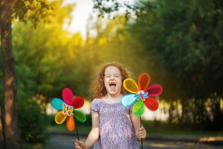 Laughing girl holding a rainbow pinwheel toys.