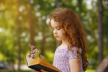 Little Girl hold bouquet of lilacs and reading the book in spring park . Retro portrait cute child in country style. Foto de archivo