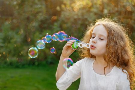 Little girl blowing soap bubbles in summer park. Banco de Imagens