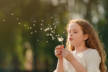Cute curly girl blowing dandelion in sunset light.