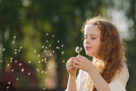 Curly girl dancing in flying dandelions outdoors.