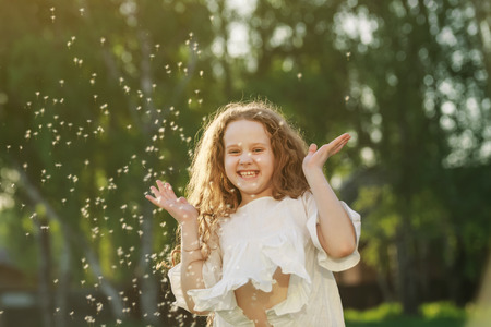 Cute curly baby with flying dandelion seed outdoors. Healthy, allergies, happy childhood concept.