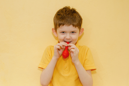 Child in yellow t-shirt inflates a red balloon on yellow background. Happy holiday concept.