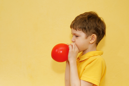 Child in yellow t-shirt inflates a red balloon on yellow background. Banco de Imagens