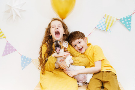 Children and their friend dog embraced and singing a song for his birthday. Party holiday concept.