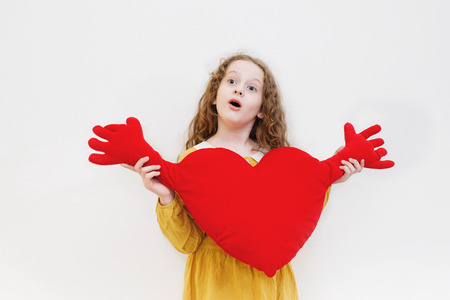 Cute girl holding red heart on light background. Love emotion, Valentines day or healthcare, medical concept. Stock Photo