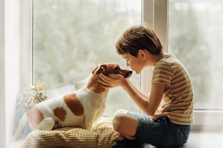 Il ragazzino bacia il cane nel naso sulla finestra. Amicizia, cura, felicità, concetto di nuovo anno.