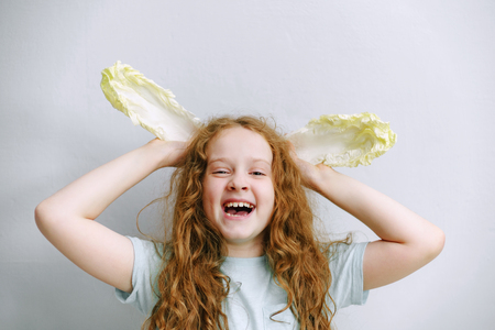 Funny girl with ears of peking cabbage. Healthy, medical, diet, vegetarian concept.