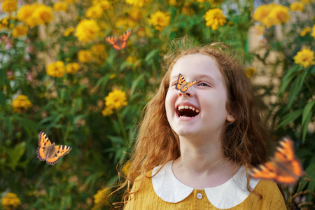 Laughing curly girl with a butterfly on his nose. Healthy smile with white teeth. Free breathing concept. Reklamní fotografie