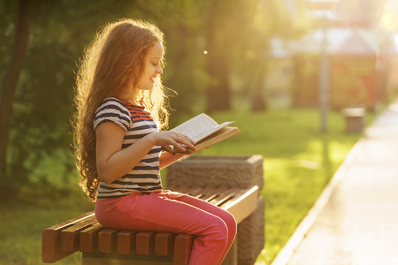 Smart little girl reading the book outdoors. Education concept.