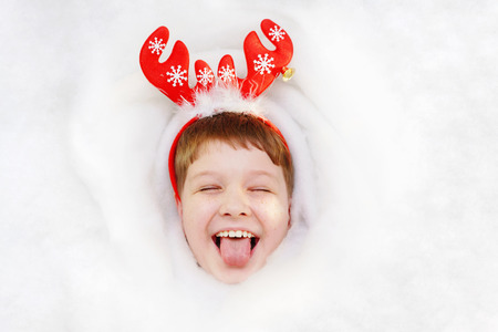 Happy child in suit reindeer stik out his tongue showing white teeth. Hight top view background. Christmas, new year holiday concept.