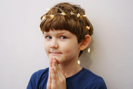 Child folded his hands in prayer, looking at the camera.