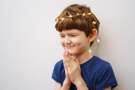 Child closed his eyes and folded his hands in prayer.