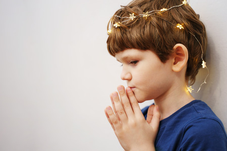 Little boy folded his hands in prayer, profile view. Religion concept.