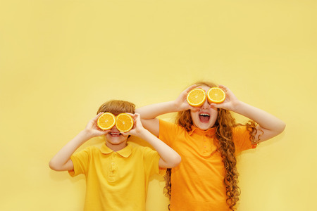 Laughing kids with orange eyes shows white healthy teeth on a yellow background. Healthy, lifestyle and a happy childhood concept. Stock fotó