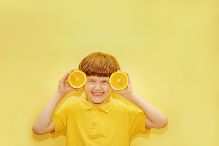 Laughing child with orange eyes shows white healthy teeth on a yellow background. Healthy, lifestyle and a happy childhood concept.