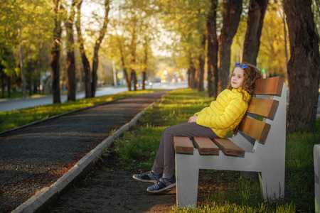 Lovely girl sitting on a bench in an autumn park.