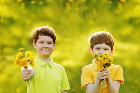 Little boys gives a bouquet yellow dandelions to his mother or girl friend. Mum, 8 march Day concept.