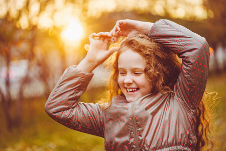 Laughing little girl in autumn park. Healthy, lifestyle concept.