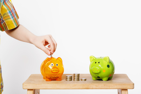 Child hand putting coin in a piggy bank. People, investments, childhood concept
