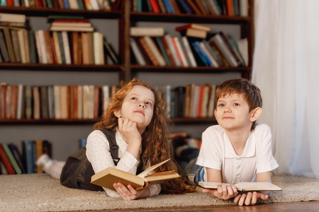 Schoolchildren dreaming and reading the book at home. Education, back to school oncept. Standard-Bild