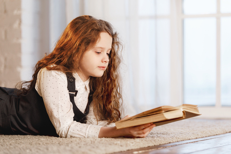 Schoolgirl reading the book at home. Education, back to school oncept.