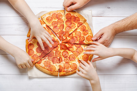 Family eating peperoni pizza. Kids and fathers holding a slice of pizza.