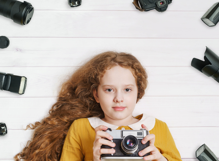 Little girl with retro photo cameras and photo accessoires lying on a wooden floor. Stockfoto