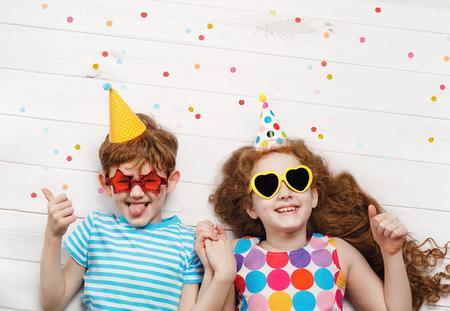 Glückliche Kinder auf Karnevalsparty, auf einem Holzboden liegend. Glückliche Kindheit, Urlaubskonzept.