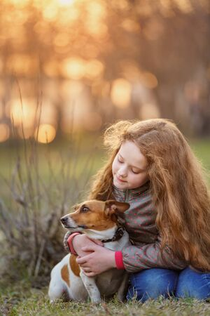 Little girl hugging her friend a dog in outdoors. Friendship, animal protection, lifestyle concept.